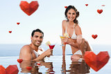 Composite image of cheerful couple having cocktails in the pool