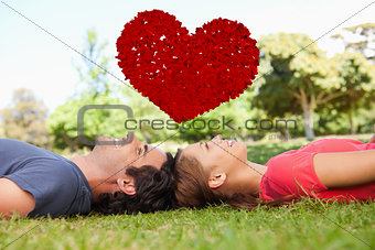 Composite image of two smiling friends looking upwards while lying head to head