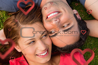 Composite image of close up two friends looking at each other while lying head to shoulder