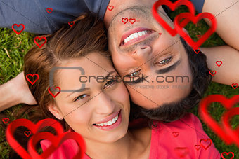 Composite image of close up of two friends looking upwards while lying head to shoulder