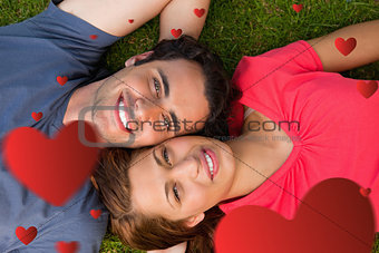 Composite image of two friends looking upwards while lying head to shoulder