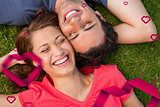 Composite image of two friends smiling while lying head to shoulder with an arm behind their head