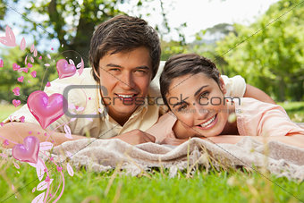 Composite image of two friends lying together on a blanket while smiling