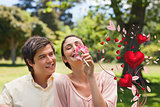 Composite image of man watching his friend while she is smelling a flower