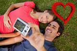 Composite image of man taking a photo with his friend while lying side by side