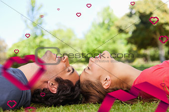 Composite image of two smiling friends with their eyes closed while lying head to head