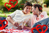 Composite image of man smiling as he looks at his friend during a picnic