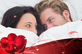 Composite image of couple under the duvet looking at each other