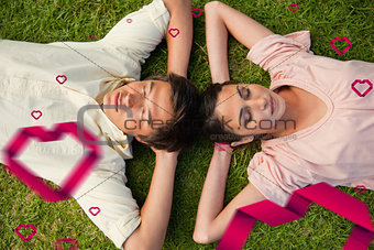 Composite image of two friends lying head to head with both hands behind their neck