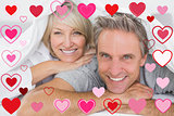 Composite image of couple smiling under the covers