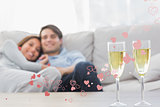 Composite image of couple resting on a couch with flutes of champagne