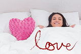 Composite image of woman lying in bed next to a fluffy heart pillow