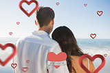 Composite image of peaceful couple looking at the ocean