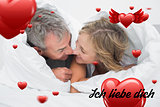 Composite image of loving middle aged couple under the duvet