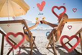 Composite image of happy couple clinking their glasses while relaxing on their deck chairs