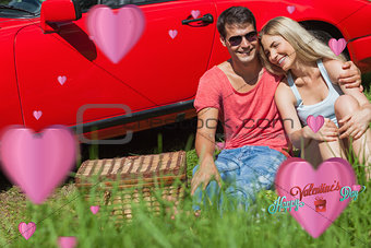 Composite image of smiling couple sitting on the grass having picnic together
