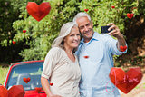 Composite image of cheerful mature couple taking pictures of themselves