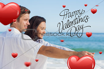 Composite image of romantic couple relaxing on the beach