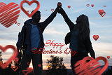 Composite image of silhouette couple holding up hands at dusk