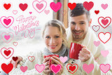 Composite image of loving couple in winter clothing with coffee cups against window