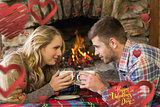 Composite image of couple with tea cups in front of lit fireplace