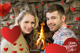 Composite image of smiling young couple in front of lit fireplace