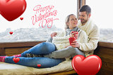 Composite image of loving couple in winter wear with cups against cabin window