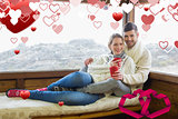 Composite image of couple in winter wear with coffee cups against cabin window