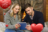 Composite image of couple using tablet pc in front of lit fireplace