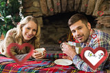Composite image of smiling couple with tea cups in front of lit fireplace
