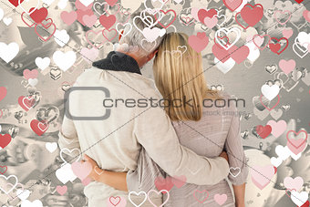 Composite image of happy couple standing with arms around