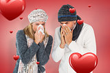 Composite image of sick couple in winter fashion sneezing