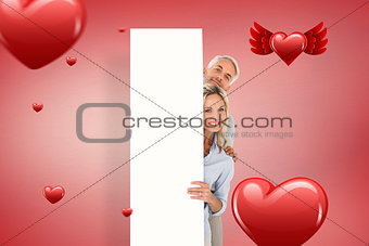 Composite image of happy couple showing large poster