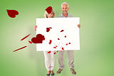 Composite image of happy couple holding large poster