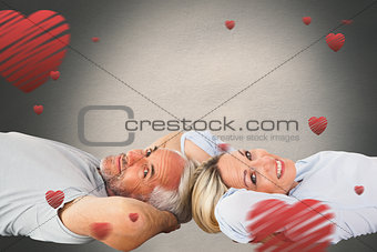 Composite image of smiling couple lying and looking at camera