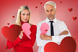 Composite image of couple not talking holding two halves of broken heart