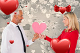 Composite image of handsome man getting a heart card form wife