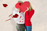 Composite image of couple embracing and holding heart over faces