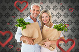 Composite image of happy couple carrying paper grocery bags
