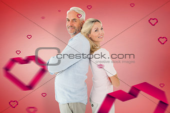 Composite image of smiling couple standing leaning backs together