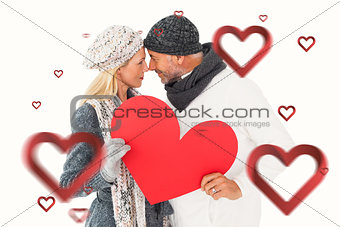 Composite image of smiling couple in winter fashion posing with heart shape