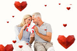 Composite image of happy couple sitting and holding present