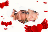 Composite image of young couple peeking through torn paper