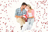 Composite image of attractive young couple sitting holding a gift