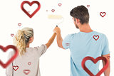 Composite image of young couple painting with roller
