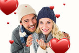 Composite image of attractive couple in winter fashion smiling at camera
