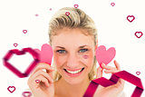 Composite image of attractive young blonde holding little hearts
