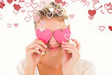 Composite image of attractive young blonde holding hearts over eyes