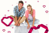 Composite image of attractive young couple sitting looking at blueprint