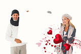 Composite image of smiling couple in winter fashion holding poster